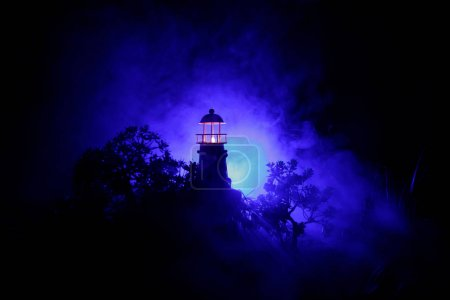 Lighthouse with light beam at night with fog. Old ...