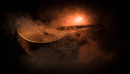 Photo for Music concept. Acoustic guitar on a dark background under beam of light with smoke. Guitar with Strings, close up. Selective focus. Fire effects. - Royalty Free Image