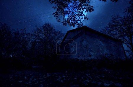 Photo pour Paysage nocturne de montagne de construction en forêt la nuit avec lune ou maison de campagne vintage la nuit avec nuages et étoiles. Froid nuit d'automne - image libre de droit