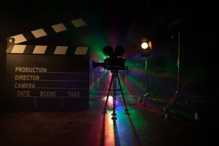 Photo pour Concept de film. Film miniature sur fond sombre avec brouillard et espace vide. Silhouette de caméra vintage sur trépied et clapet. Concentration sélective - image libre de droit