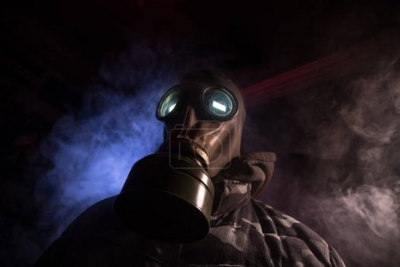 Photo for Environmental disaster. Post-apocalyptic survivor in gas mask on a dark background. Dramatic portrait of a man wearing a gas mask. Means for radiation protection. Selective focus - Royalty Free Image