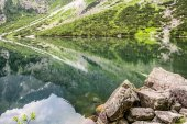 Landscape of mountain lake with clear water in emerald color in Tatra Mountains over Morskie Oko