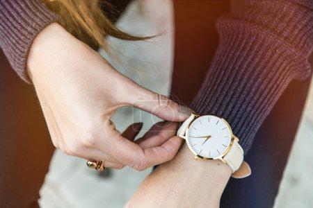 Photo pour Entreprise jeune femme tenant sa montre dorée. Classé dans des couleurs chaudes. - image libre de droit