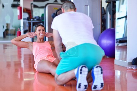 Personal trainer helping a woman in the gym