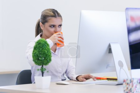 designer woman sitting at home office desk with cup