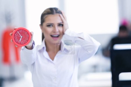 Businesswoman with clock at office