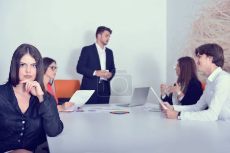 Group of business colleagues listening to a businessman during a meeting.