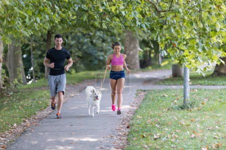 young couple with dog running in park,