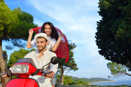 Beautiful young couple riding on a scooter