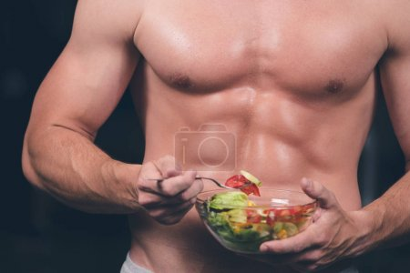 Healthy man holding a fresh salad bowl