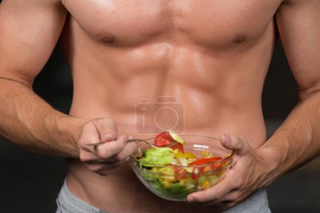 healthy man holding a fresh salad bowl