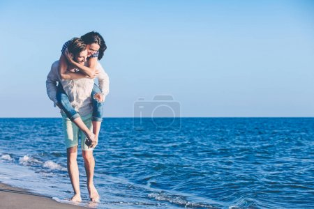 Man giving piggy back to girlfriend at the beach