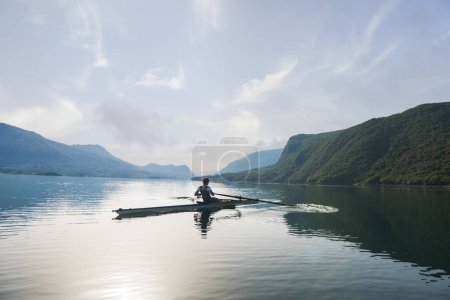 Young single scull rowing on lake