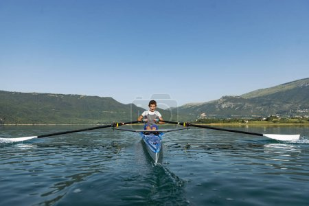 The young sportsman is rowing on the racing kayak