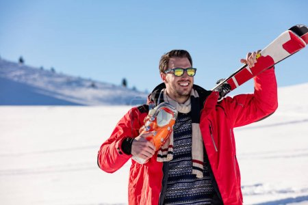 Healthy man with pair of skis in hands