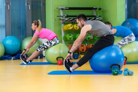 Group exercising on Swiss ball at gym