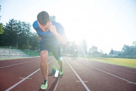 Photo for Sprinter leaving starting blocks on the running track. Explosive start - Royalty Free Image