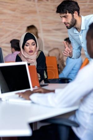 Photo pour Divers étudiants utilisant ordinateur portable et parler, apprendre à échanger des idées . - image libre de droit