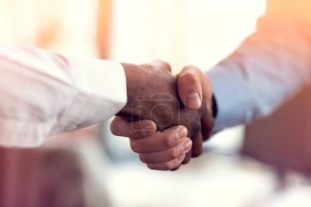 Photo pour Gros plan de blanc et noir serrant la main sur une affaire . - image libre de droit