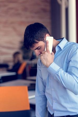 Portrait of a cheerful smiling men office worker talking on mobile phone while standing in modern office space