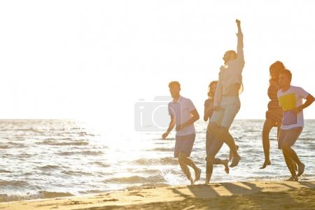 Photo for Friends fun on the beach under sunset sunlight - Royalty Free Image