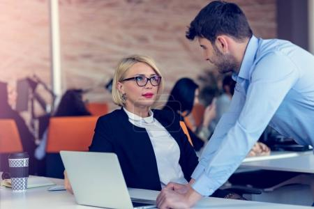 Skilled professional blonde female CEO explaining to young male employee requires and strategy