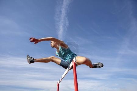Photo pour Vue à faible angle d'un athlète masculin déterminé sautant par-dessus un obstacle . - image libre de droit