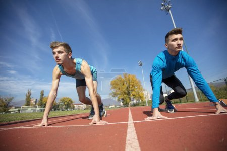 Photo for Athletes at the sprint start line in track and field. - Royalty Free Image