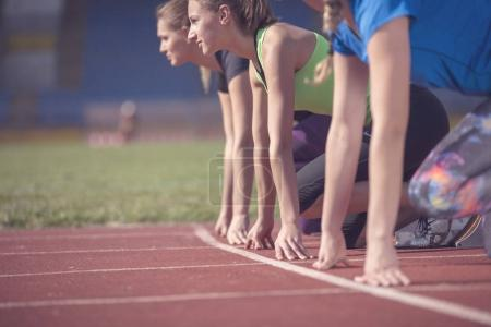 Photo for Women ready to race on track field. - Royalty Free Image