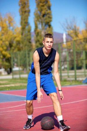 Photo pour Beau mâle jouant au basket en plein air. sur le terrain - image libre de droit
