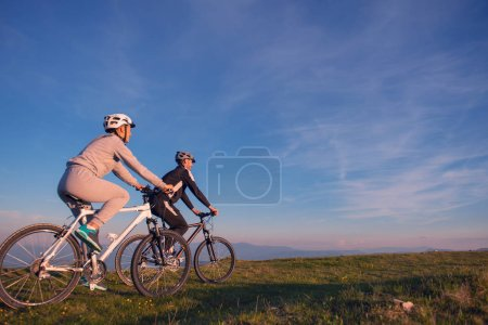 Photo for Happy mountainbike couple outdoors have fun together on a summer afternoon sunset. - Royalty Free Image
