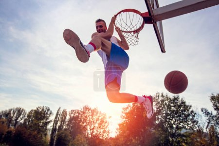Photo for Young man jumping and making a fantastic slam dunk playing streetball, basketball. Urban authentic - Royalty Free Image