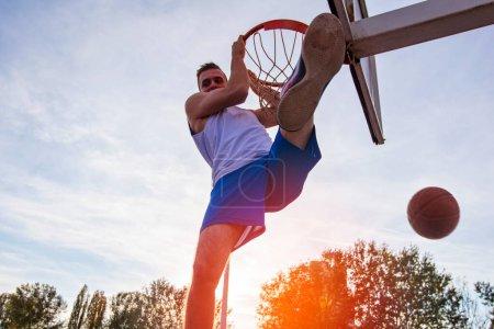 Foto de Joven saltando y haciendo un fantástico slam dunk jugando streetball, baloncesto. Auténtico urbano - Imagen libre de derechos