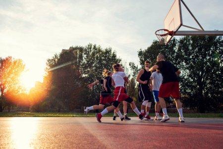 Photo pour Groupe de jeunes amis jouant au basket-ball Match. - image libre de droit
