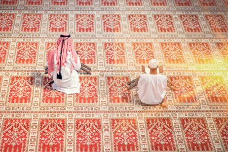 Photo for Two religious muslim man praying together inside the mosque. - Royalty Free Image