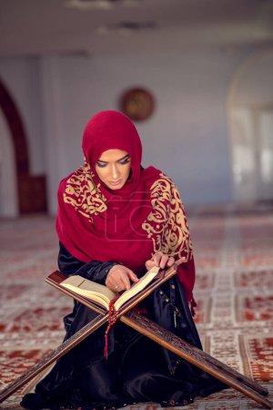 Photo pour Jeune femme musulmane lisant le Coran dans la mosquée et la lumière du soleil tombant de la fenêtre. - image libre de droit