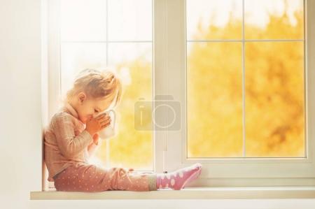 Photo pour Petite fille mignonne en pyjama assise près d'une grande fenêtre jouant souriant en appréciant la maison. Coupe Cacao debout sur la fenêtre. Automne Saison Intérieur Famille Textile industrie Vacances Personnes concept - image libre de droit