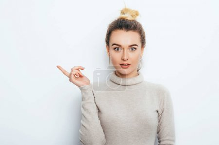Photo for Look There! Surprised Attractive young female lady wearing in sweater with hair bun showing emotions on white wall. Shocked woman points with forefinger at copy space on white background. Amazement - Royalty Free Image