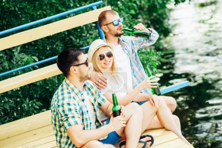 Group of friends two men and woman hanging out on nature with bottles of beer. Spending time with beer on beach and having fun! Drinks People Emotions Barbecue Summer Lifestyle concepts
