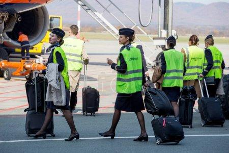 Photo pour Russie, Vladivostok, 13 / 10 / 2017. De belles hôtesses habillées en uniforme bleu foncé officiel d'Aeroflot Airlines et des gilets réfléchissants vont à l'avion sur l'aérodrome. Equipage d'avion. Aviation et transports . - image libre de droit