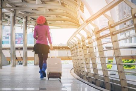 Photo pour Voyageur femme marchant dans l'allée de l'aéroport avec le sac de voyage ou de bagages. Voyageur voyager à l'étranger par le terminal de l'aéroport international. Concept de voyage femme, style de vie avec sac de voyage. - image libre de droit