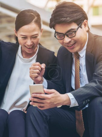 Happy business man and woman looking at phone