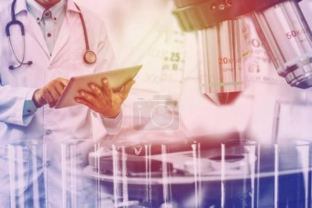 Photo pour Concept de recherche et développement en sciences médicales - Médecin tenant un ordinateur tablette avec instrument scientifique, microscope et tube à essai chimique en arrière-plan de laboratoire . - image libre de droit