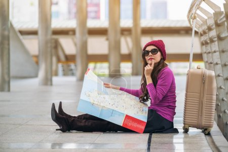 Photo for Woman traveller looking at travel map in airport walkway with bag or luggage. She is lost or using map to plan travel route for the next destination. Concept of single woman travel alone. - Royalty Free Image