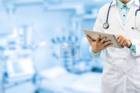 Photo for Male doctor working on computer tablet in the hospital or office background. Concept of medical data analysis and healthcare business. - Royalty Free Image