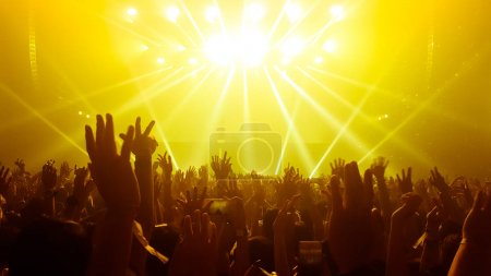 Photo for Happy people dance in nightclub party concert and listen to music from DJ on the stage in background. Cheerful crowd celebrate Christmas and New Year party 2018. Young people lifestyle and nightlife. - Royalty Free Image