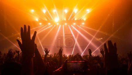 Photo pour Gens heureux dansent en soirée concert de boîte de nuit et écoutent la musique de Dj sur la scène en arrière-plan. Foule joyeuse célèbrent la fête de Noël et nouvel an 2018. Les jeunes de style de vie et la vie nocturne. - image libre de droit