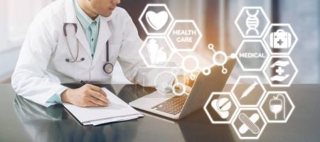 Photo for Medical Concept - Doctor working in hospital with computer and writing paperwork illustrated with medical icons pop up from doctors hand about healthcare pharmacy business and doctoral education. - Royalty Free Image