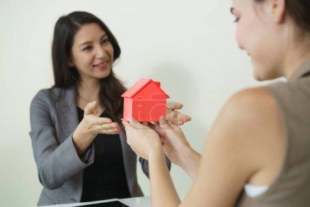 Photo pour L'agent immobilier remet une petite maison à sa cliente. Concept de contrat de vente immobilière . - image libre de droit