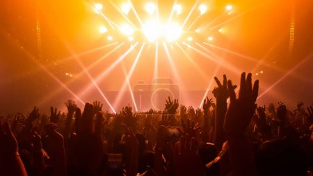 Photo for Silhouettes of concert crowd in front of bright stage lights. Nightlife and concert party concept. - Royalty Free Image